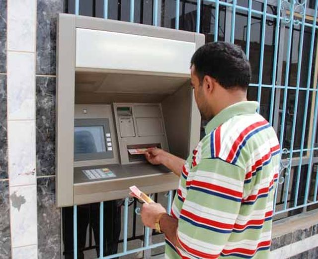 Customer withdrawing dinars from an ATM