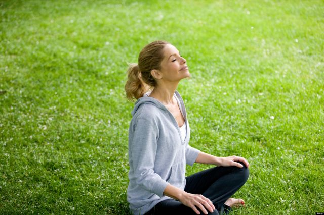 A mid adult woman sitting on the grass