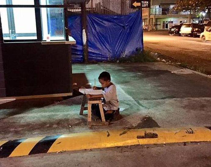 Ce s-a ales de baietelul fotografiat in timp ce-si facea temele pe strada, la lumina unui bar?!