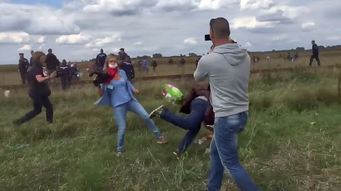 VIDEO – O unguroaica angajata la o televiziune LOVESTE CU PICIORUL un imigrant care-si cara copilul!