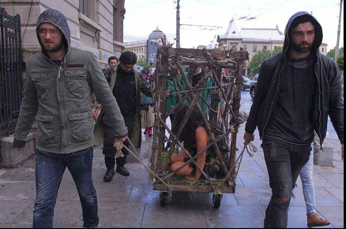 FOTO – VIDEO Femeie aproape dezbracata plimbata intr-o cusca prin Bucuresti! Vezi ce-a facut tanara!